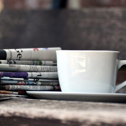 Eine Tasse und Zeitungsseiten